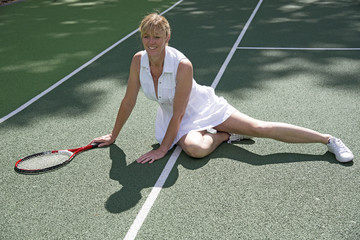Female tennis player fallen on the court sitting on ground