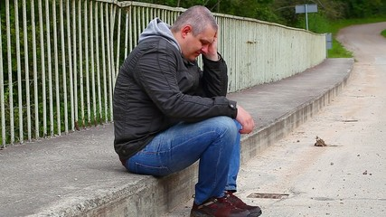 Depressed man sitting on the bridge