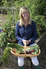 Woman gardener holding a trug and fresh vegetables
