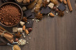chocolate, cocoa, nuts and spices on wooden background, top view - 69575823