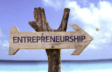 Entrepreneurship wooden sign with a beach on background