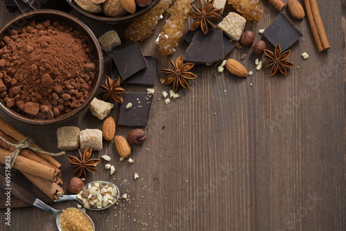 chocolate, cocoa, nuts and spices on wooden background, top view