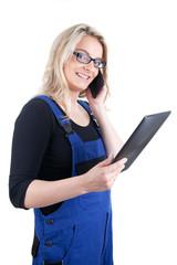 Frau im Blaumann mit digitalem Tablet und Mobiltelefon