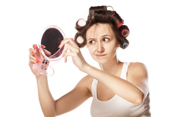 dissatisfied young woman without makeup and with hair curlers