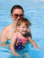 Family in swimming pool playing
