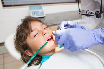 Pediatric dentist examining a little boys teeth