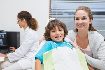 Boy and mother smiling at camera with dentist