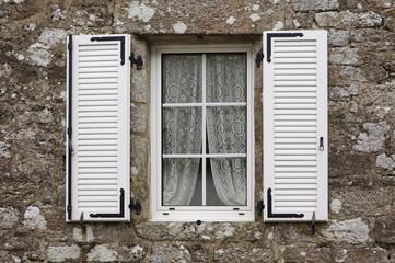 Granitfassade mit modernem Kunststofffenster und PVC-Klappladen