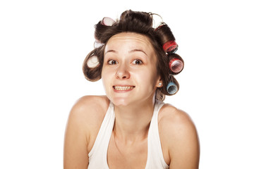 unsure and smiling young woman  with hair curlers