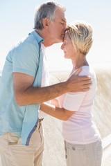 Happy senior man giving his partner a kiss on forehead