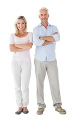 Smiling couple standing with arms crossed