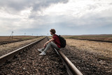 Teen girl with problems sitting on rail road poster