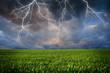 Leinwandbild Motiv Thunderstorm with lightning in green meadow