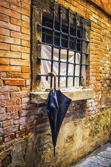 parasol by the window on the background of an old brick wall