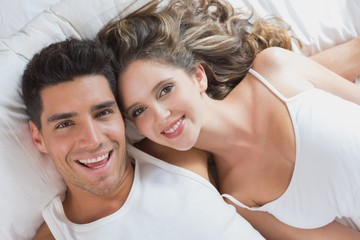 Young couple lying in bed at home