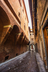 A lone passerby with an umbrella on a narrow street in the old c