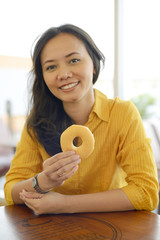 Pretty Young Attractive Woman Eating Donut  At Cafe
