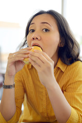Pretty Young Woman Eating Burger In Cafe