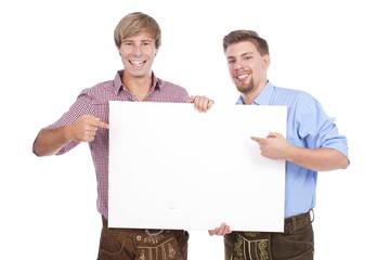Zwei Männer in Tracht zeigen auf weiße Fläche