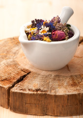 Dried herbs and flowers in mortar on wooden board