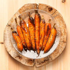 Baked carrots on wooden board in rustic style