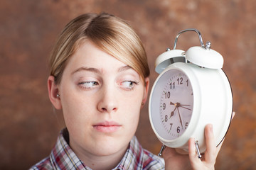 Young woman holding the alarm clock