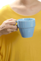 Woman Hand Wearing Orange Shirt Holding Blue Cup Of Coffee