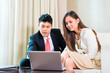 Businesspeople in Asian hotel room with laptop