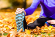 Sportlerin beim Stretching im Herbstlaub