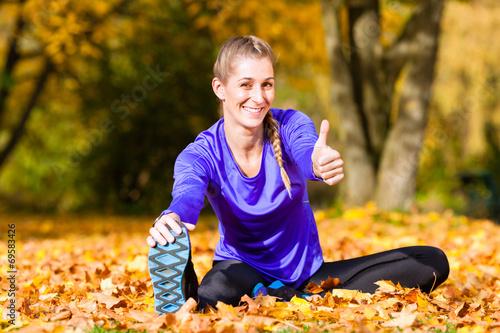canvas print picture Sportlerin beim Stretching im Herbstlaub