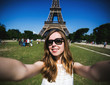 Woman tourist at Eiffel Tower smiling and making travel selfie. - 69584207