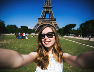 Woman tourist at Eiffel Tower smiling and making travel selfie.