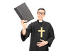 Happy young priest holding a holy bible
