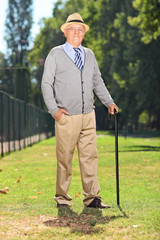 Senior with cane posing in a park