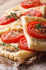 Homemade puff pastry with tomatoes, cheese and herbs vertical