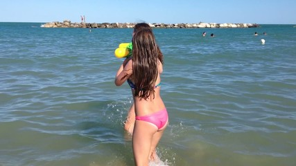 Ragazze giocano in mare con pistole a spruzzo d'acqua