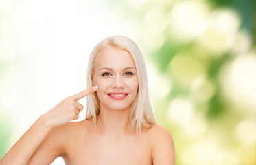 smiling young woman pointing at her cheek