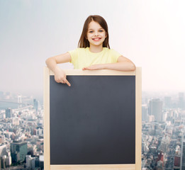 happy little girl pointing finger to blackboard