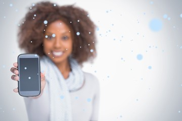 Composite image of woman with afro showing her smartphone