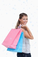 Composite image of portrait of a woman holding shopping bags