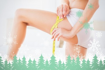 Composite image of thin woman measuring her thigh