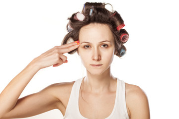 unhappy woman with hair curlers make suicidal gesture