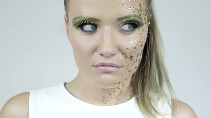 Sexy caucasian woman in golden make-up posing in studio.