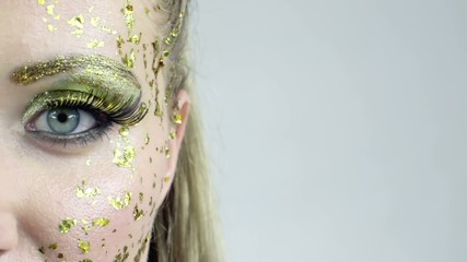 Half face of woman in golden make-up. Copy space background.