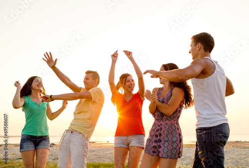 canvas print picture smiling friends dancing on summer beach
