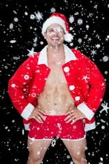 Smiling muscular man posing in sexy santa