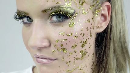 Face of beautiful woman in golden make-up posing in studio.