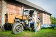 Frau mit alten Trecker auf dem Land