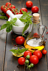 Olive oil bottle, cherry tomatoes and fresh basil