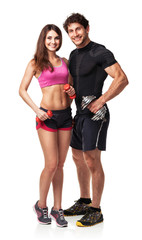 Athletic couple - man and woman with dumbbells on white